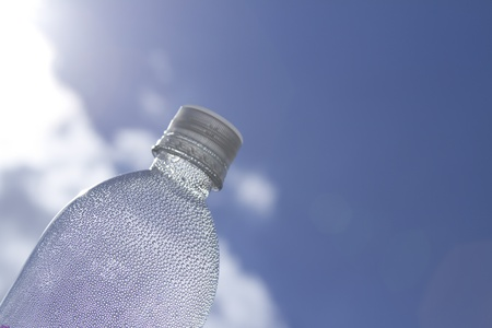 refreshing water droplets in a non descript bottle with a sky background