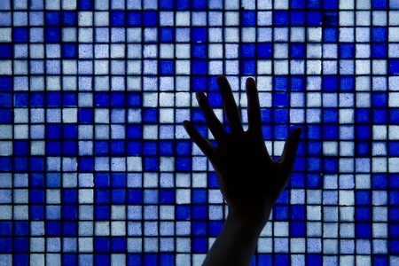 mosaic wall of tiles that looks like data bytes, with hand silhouette