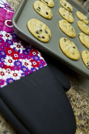 cookies on a baking pan with oven mitten Stock Photo