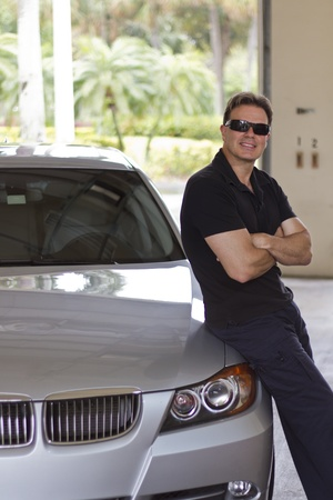 rich man: young rich man next to new car