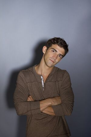 young man thinking with arms crossed photo
