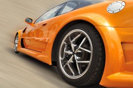 orange extreme car with modern wheel rims in motion