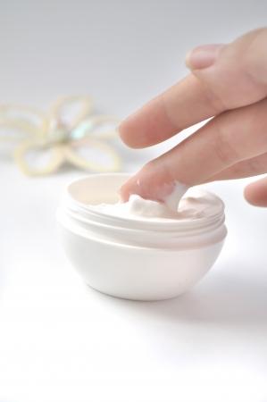 crème: immagine delle dita tenendo la mano crema con decorazione floreale sullo sfondo