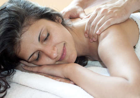 A woman with arms down receiving a shoulder massage