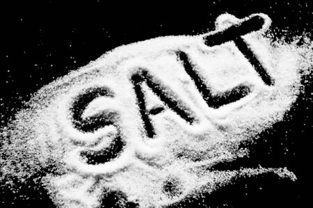 Salt written on counter in spilled salts from shaker  photo