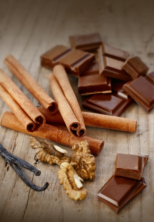 confectionary: confectionary products  Chocolate, cinnamon, walnuts and vanilla on wooden table Stock Photo