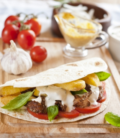 gyros: tortilla with chicken meat, fries and basil Stock Photo