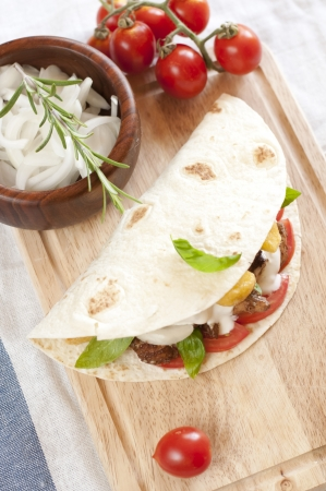 tortilla with chicken meat, fries and basil photo