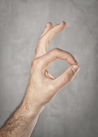 Ok! Hand gesture on gray background