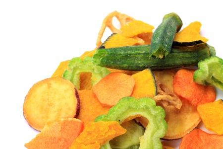 Tomé chips de verduras en un fondo blanco.