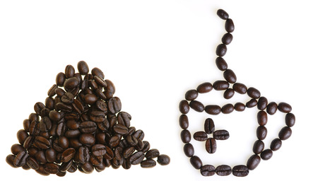 Pile of coffee beans and steaming cup of coffee on white background