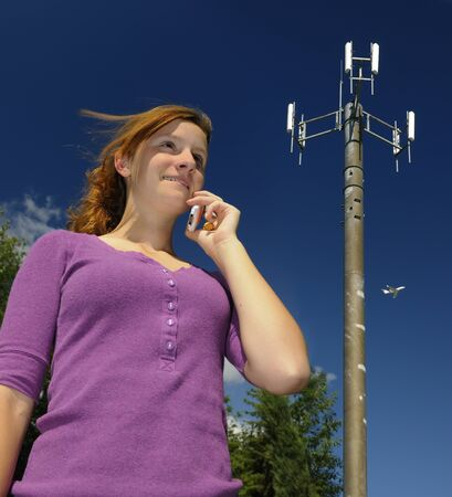 Young girl talking on a cellphone beside a wireless communications tower LANG_EVOIMAGES