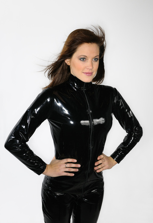 wind blown: Young woman arms akimbo in a black plastic catsuit with hair blowing in wind on white background