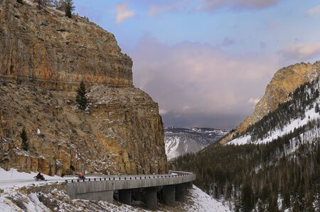 iron oxide: Snowmobilers on Grand Loop Road at Golden Gate entering Kingman Pass at sunset during winter