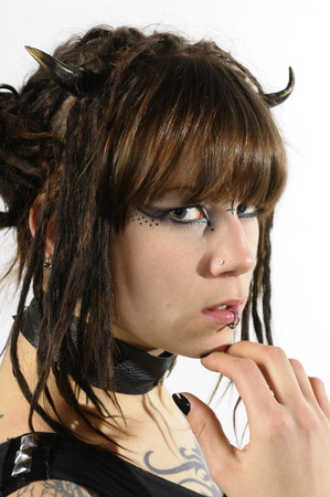 Close up of a young heavy metal fan girl with horns piercings and tattoos on a white background
