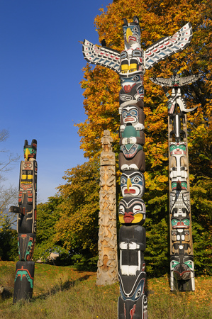 thunderbird: Totem polies in Stanley Park Vancouver with raven and changing maple leaves in Autumn on blue sky LANG_EVOIMAGES
