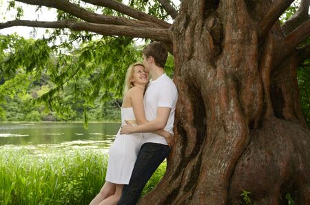 Happy couple embracing under a large Dawn Redwood tree on the shore of a lake