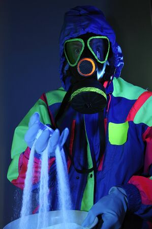 Hooded man in gas mask with gloves sifting white crystals under UV light LANG_EVOIMAGES