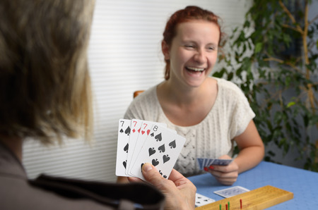 dealt: Laughing daughter playing Cribbage card game with mother at home