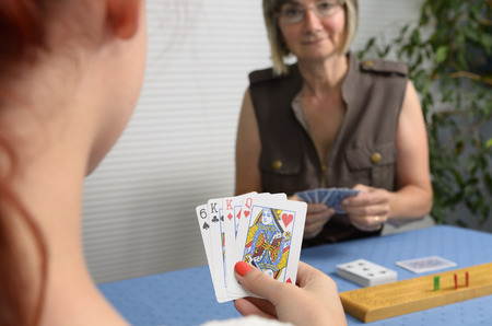 dealt: Mother playing Cribbage card game with young daughter at home