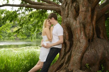 Happy couple embracing and laughing under a large Dawn Redwood tree on the shore of a lake LANG_EVOIMAGES