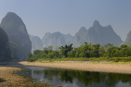 Pebble shore of the Li River with limestone Karst cones and peaks in the haze