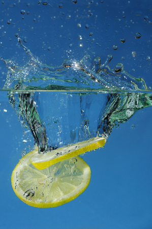 Pair of lemon slices splashing into water with a blue background LANG_EVOIMAGES