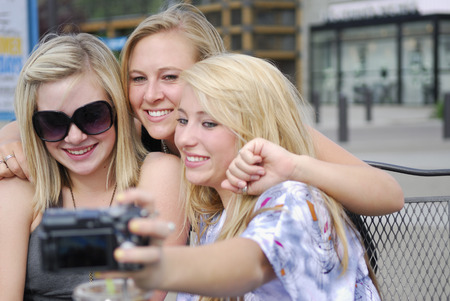 say cheese: Three girls taking a self portrait with a digital camera LANG_EVOIMAGES