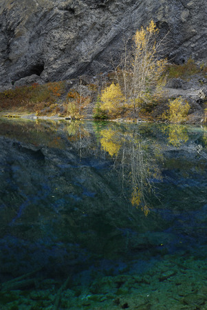 canmore: Yellow Aspen leaves reflected in the Indigo blue waters of Grassi Lakes