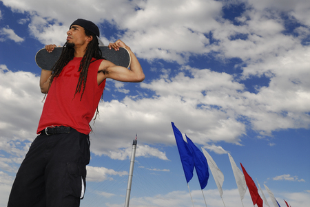 panache: Black male skateboarder posing against a blue clouded sky and flags
