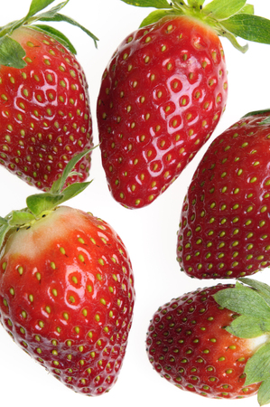 Five strawberries close up on a white background