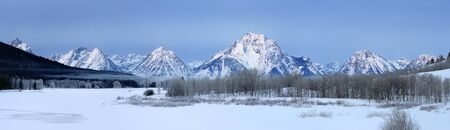 Wide panorama of mist over Oxbow Bend at sunrise during cold winter morning