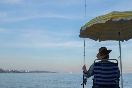 Man sitting fishing on the seashore Banco de Imagens