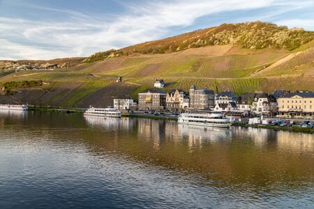 View at the city of Bernkastel-Kues at river Moselle with passenger ships and mountains with vineyards in the background