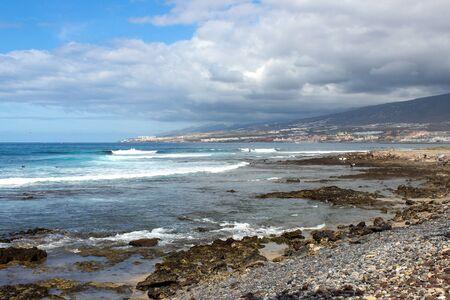 Kamienista plaża w Playa de Las Americas na Teneryfie Wysp Kanaryjskich z błękitną wodą i błękitnym niebem