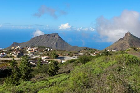 Landscape with green plants in the front, houses and mountains in background on Canary Island Tenerife