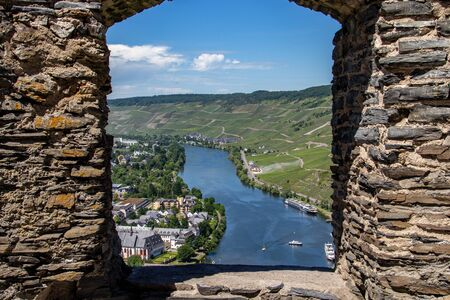 View at the valley of the river Moselle and the city of Bernkastel-Kues from Landshut castle through a window in the wall Stock Photo