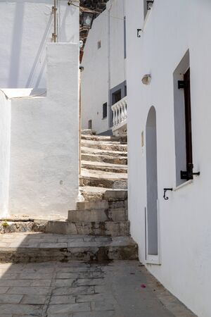 Narrow street with stairs and white houses in Lindos on Greek island Rhodes Banco de Imagens