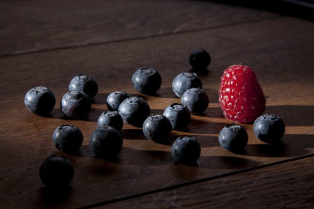 sidelight: still life with some blueberries an one raspberry in a cone of light