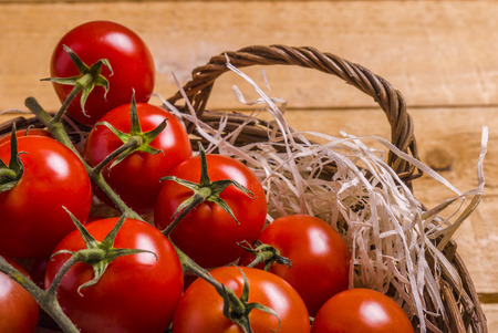 wicker basket nest with tomatos on a wooden board