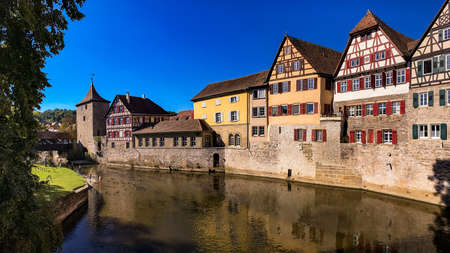 Idyllic panorama in a German old town on a river with city wall and half-timbered houses Standard-Bild