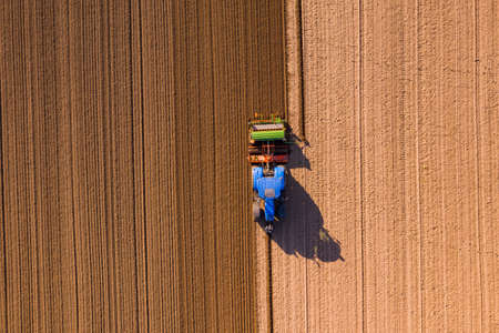 A farmer with a tractor plows a field so that it can lie fallow in winter