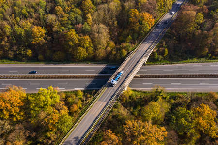 A road crossing through a German mixed forest seen from above in autumn