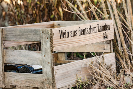 An old wooden box lies in the nature with wine from Germany