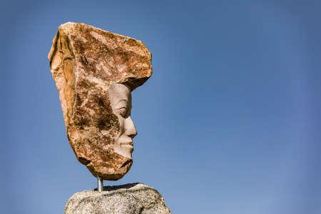 Striking granite stone statue against a blue sky Standard-Bild