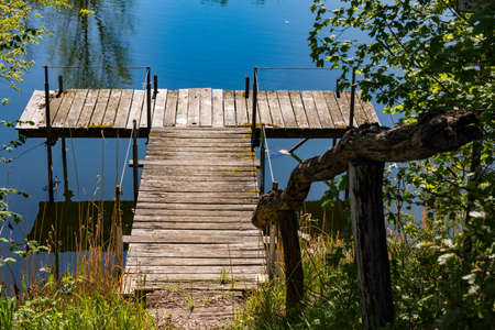 A wild and romantic pier on a natural lake with an old jetty in the sunshine Standard-Bild