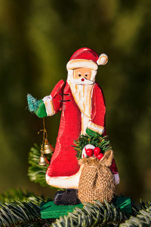 A classic wooden Santa Claus with bells and sack isolated against a natural green background