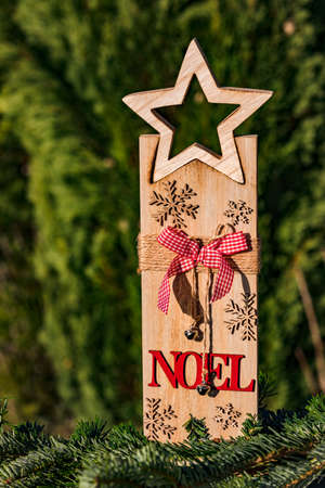 Christmas wooden decoration with the inscription Noel and a red bow and a star made of wood Standard-Bild