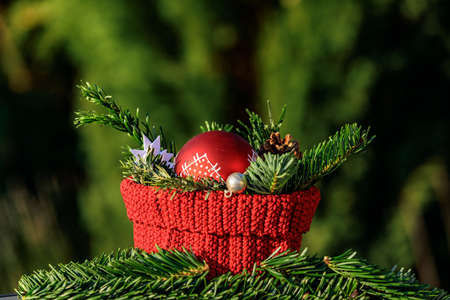 Christmas decoration with a red basket, fir branches and a red Christmas tree ball against a green background