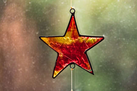 A glass star framed in black metal is a beautiful Christmas ornament in the backlight